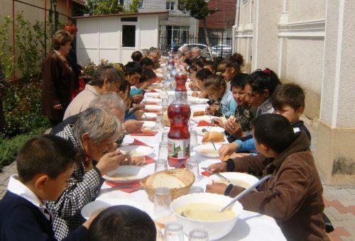 Masă caldă în curtea bisericii, pentru nevoiașii din Dej